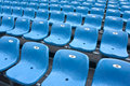 Grandstand of stadium diagonally empty plastic chairs blue color on grandstands Stock Photos