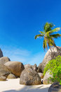 Granite boulders on the carana beach of mahe island seychelles seascape with large and blue summer sky typical view Royalty Free Stock Images