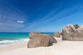 Granite boulders on the carana beach of mahe island seychelles seascape with large and blue summer sky view Stock Image