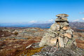 Granite stone cairn as a navigation mark on the top of norwegian mountain Stock Photos