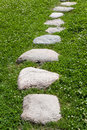 Granite stone pathway on green grass Royalty Free Stock Images