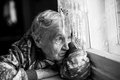 Granny older woman sadly looking out the window. Royalty Free Stock Photo
