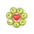 Granny smith apple green with heart shape on white plate Stock Images