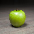 Granny smith green apple against wooden background Royalty Free Stock Image
