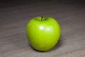 Granny smith green apple against wooden background Royalty Free Stock Photo