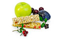 Granola bar with lingonberries and fruit green apple plum cherry branches leaves berries a light shade on white background Royalty Free Stock Photography