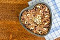 Granola in a heart-shaped baking sheet on a wooden table. Food Concept