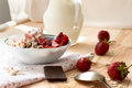 Granola with strawberries yogurt and strawberry topping milk j oatmeal jug for breakfast toned image selective focus Royalty Free Stock Photos