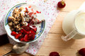Granola with strawberries yogurt and strawberry topping milk j oatmeal jug for breakfast toned image selective focus Royalty Free Stock Photography