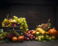 Grape, apples and autumn fruits and vegetables in an iron bowl with a sunflower on a wooden table on a dark wall background