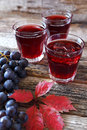 Grape juice, black grapes and autumn leaves Royalty Free Stock Photo