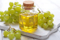 Grape seed oil in a glass jar on wooden background Royalty Free Stock Photography