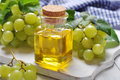 Grape seed oil in a glass jar on wooden background Royalty Free Stock Images