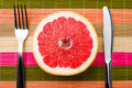 Grapefruit between fork and knife Royalty Free Stock Photo
