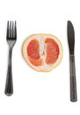 Grapefruit with fork and knife Royalty Free Stock Photo