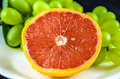 Grapefruit freshly cut with green grapes in the background Royalty Free Stock Photo