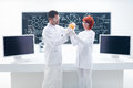 Grapefruit laboratory analysis general view of two people holding a in a chemistry lab with a working table and a blackboard on Stock Photography