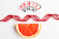 Grapefruit with measuring tape on weight scale. Dieting Royalty Free Stock Photo