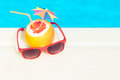 Grapefruit and sunglasses at the edge of swimming pool Royalty Free Stock Photo