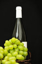 Grapes in a basket and a bottle green of wine on dark background Royalty Free Stock Image