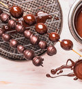 Grapes in chocolate on wooden skewer preparation Stock Images