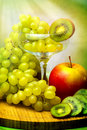 Grapes in glass, red apple and kiwi Royalty Free Stock Photography