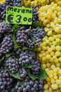 Grapes on sale bunches of black and green at euros per kilogram laid out a market stall Stock Photo