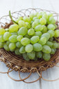 Grapes in a wicker plate bunch of on white wooden background Royalty Free Stock Image
