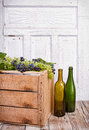 Grapes on wooden crate vine sitting with empty wine bottles Royalty Free Stock Images