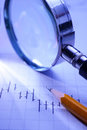 Graph magnifying glass and pencil in a beam of light across a blue background depicting business analysis planning strategy Stock Image