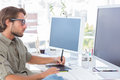 Graphic artist using graphics tablet at his desk Royalty Free Stock Photos
