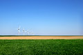 Graphic modern landscape of wind turbines aligned in a field green and yellow Stock Images