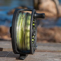 Graphite fly reel a on a wooden bench Royalty Free Stock Photo