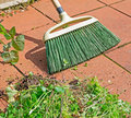 Grass broom red floor Royalty Free Stock Image