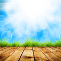 Grass fresh spring green with blue bokeh and sunlight and wood floor natural background Royalty Free Stock Images