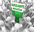 Grass roots marketing campaign local advertising word of mouth a man holding a sign in a crowd to illustrate and spreading to Royalty Free Stock Photo