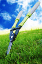 Grass shears scissors to cut the in the sky as a backdrop Royalty Free Stock Photos