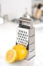 Grater with lemon on the kitchen table selective focus Stock Photo
