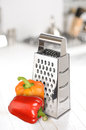Grater with peppers on the kitchen table selective focus Royalty Free Stock Images
