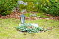 Grave with lantern small and wreath wreath is made of pine twigs and cones stone wall moss in background Royalty Free Stock Photo