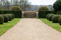 Gravel path in garden wide formal with clipped box buxus sempervirens and yew taxus baccata shrubs Stock Photography
