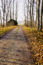 Gravel road, abandoned house and autumn trees. Stock Photo