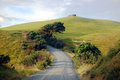 Gravel road turn left at rural area near water tank on hill top dargaville new zealand Stock Images