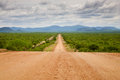 Gravel road with zebra mountains in namibia the north of the the background Royalty Free Stock Image