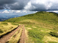 Gravel track across mountains with dramatic clouds Royalty Free Stock Photo