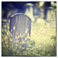 Graveyard tombstone and graves in an ancient church with instagram style filter effect Stock Images