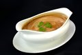 Gravy bowl in a with parsley on a black background Royalty Free Stock Image