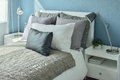 Gray, dark gray and beige pillows on bed with blue wall Royalty Free Stock Photo