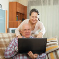 Gray haired man and mature woman working at laptop middle aged men women sitting on couch with Royalty Free Stock Photos