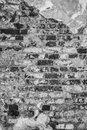 Gray texture of an old wall of an ancient building with a ruined plaster layer and cracked bricks